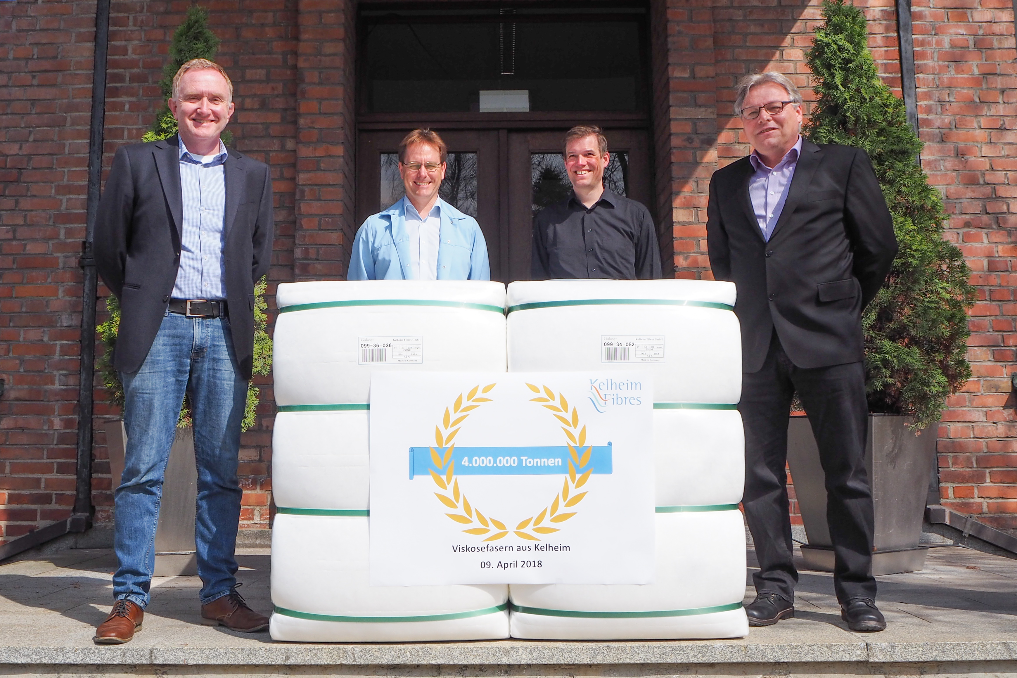 Production manager Konrad Brunner (far right) and a part of his team present the 4,000,000th tonne of viscose fibres from Kelheim.